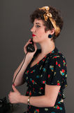 Pinup Girl in Flowered Outfit on Phone - Serious Royalty Free Stock Photography