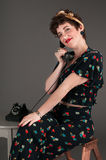 Pinup Girl in Flowered Outfit Smiles Gently on the Phone Royalty Free Stock Photography