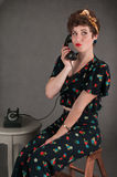 Pinup Girl in Flowered Outfit Smirks with Phone Royalty Free Stock Images