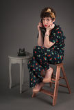 Pinup Girl in Flowered Outfit Ultra Bored on the Telephone Royalty Free Stock Photos