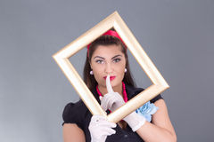 Pinup girl with a frame around her face and finger on lips Stock Photo