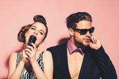 Pinup girl and man on pink, radio. Pinup girl and men on pink, radio. Music and love, security. Beauty, vintage fashion, music band. Singer men and women with royalty free stock image