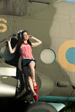 Pinup girl. Outdoors pin-up portrait of young caucasian woman in red retro dress on airplane A beautiful young female model in a pin-up type of dress poses next Stock Image