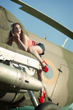 Pinup girl. Outdoors pin-up portrait of young caucasian woman in red retro dress lying on airplane A beautiful young female model in a pin-up type of dress poses Royalty Free Stock Photo