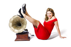 Pinup girl in red dress playing classical music. Isolated photograph of a pretty and young pinup girl in rockabilly dress kicking up a pose next to antique Royalty Free Stock Image