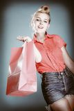 Pinup girl with shopping bag buying clothes. Sale Stock Image