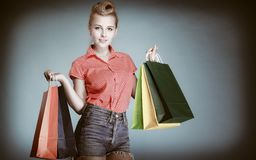 Pinup girl with shopping bags buying clothes. Sale Royalty Free Stock Image