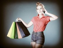 Pinup girl with shopping bags calling on the phone Royalty Free Stock Photo