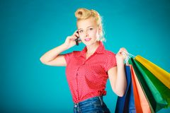 Pinup girl with shopping bags calling on phone Stock Image