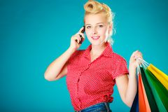 Pinup girl with shopping bags calling on phone Stock Photo