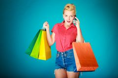 Pinup girl with shopping bags calling on phone Royalty Free Stock Image