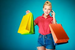 Pinup girl with shopping bags calling on phone Royalty Free Stock Photos