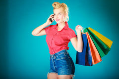 Pinup girl with shopping bags calling on phone Royalty Free Stock Photo