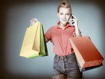Pinup girl with shopping bags calling on the phone Royalty Free Stock Images
