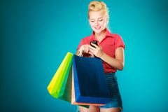 Pinup girl with shopping bags texting on phone Stock Photo
