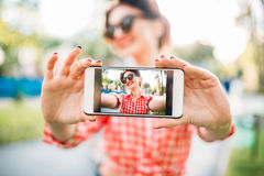 Pinup girl shows on phone outdoors selfie stock image