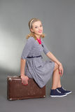Pinup girl sitting on brown retro suitcase Stock Photography