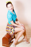 Pinup girl sitting on the sewing machine box Stock Image