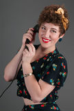 Pinup Girl Smiles While on Black Telephone Royalty Free Stock Images