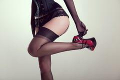 Pinup girl in vintage nylon stockings holding high heel shoe Royalty Free Stock Photos