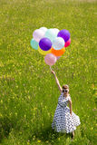 Pinup Girl with a white petticoat dress and balloons on the mead Royalty Free Stock Image