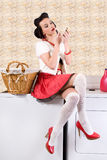 Pinup housewife in the laundry. Pinup housewife is refreshing her lipstick sitting at the washer in the laundry room Royalty Free Stock Image