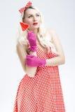 Pinup-kaukasische blonde Frau mit roter süßer Süßigkeit Stockbilder