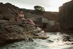 Pinup look dressed girl sitting in the rocks. Stock Image
