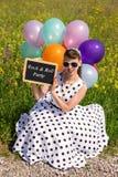 Pinup-Mädchen mit Ballonen in der Natur, die einen Schiefer mit Text hält Lizenzfreies Stockfoto