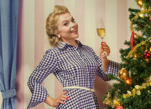 Pinup x-mas. Portrait of nice young woman hanging around christmas tree on x-mas  eve Royalty Free Stock Images