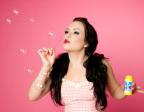 Pinup Model Blowing Soap Bubbles Stock Image