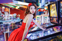 Pinup Play pinball. Style pinup girl in red dress, play pinball stock photos