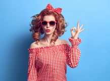 PinUp Beauty Girl Blowing lips, showing OK sign. PinUp Portrait Beauty Redhead Girl Blowing lips. Fashion Playful Woman showing OK sign. Stylish Curly hairstyle Stock Photography