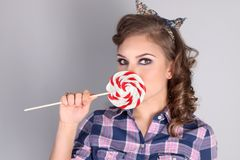 Pinup pretty girl in checkered shirt poses. With lollipop in studio stock photography