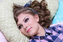 Pinup pretty girl in checkered shirt is on soft pillows Stock Image