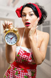 Pinup sensual girl in apron holding alarm clock Stock Photos