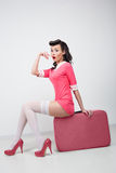 PinUp sexy girl with pink suitcase. Traveling bag Royalty Free Stock Image