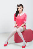 PinUp sexy girl with pink suitcase. Royalty Free Stock Image