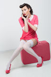 PinUp sexy girl with pink suitcase. Stock Photo
