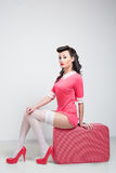 PinUp sexy girl with pink suitcase. Stock Image