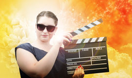 Pinup style girl in sun glasses with clapper board Royalty Free Stock Photo