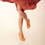 Pinup style. female legs in dance. Vintage pinup style. female legs in dance on pink. Girl in retro spotted red dress and orange high heels dancing. Party royalty free stock image