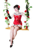 Pinup on Swing. A vintage inspired, burlesque pinup on a rambling rose covered swing. Shot on white background royalty free stock image