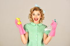 Pinup woman hold soup bottle, duster. Retro woman cleaner on grey background. Housekeeper in uniform with clean spray, duster. Cleanup, cleaning services, wife royalty free stock photo