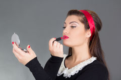 Pinup woman putting red lipstick Stock Photo