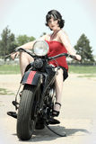 Pinup Woman and Motorcycle. A woman sits on a vintage motorcycle Royalty Free Stock Images
