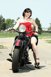Pinup Woman and Motorcycle. A pinup woman poses next to a vintage motorcycle royalty free stock photo