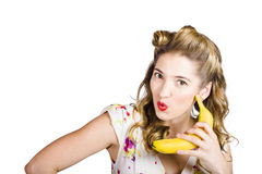 Pinup woman ordering organic fruit on banana phone Stock Photo