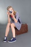 Pinup woman with camera sitting on brown retro suitcase Stock Image
