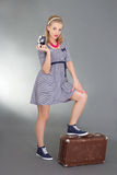 Pinup woman posing with camera and brown retro suitcase Stock Image